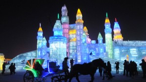 A horse carriage carrying tourists travels past ice sculptures during the lights testing period of the 14th Harbin Ice and Snow World in Harbin