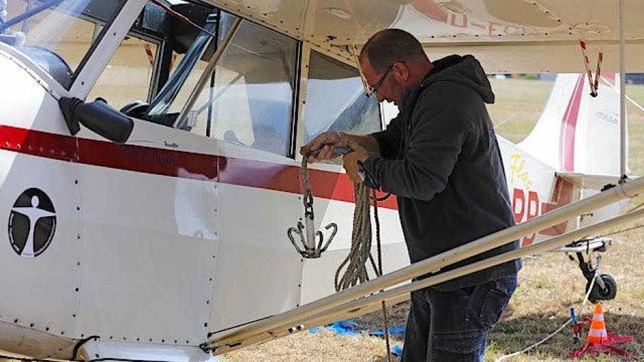 Da das Banner zu schwer und zu voluminös ist, um bereits beim Start vom Boden weg mitgezogen zu werden, muss sich der Pilot vor jedem Flug einer besonderen Prozedur unterziehen
