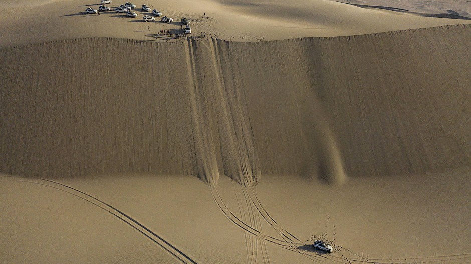 Die Fahrzeuge stürzen sich in der Düne nach unten, oben filmt die Drohne die Mutprobe in sicherem Abstand.