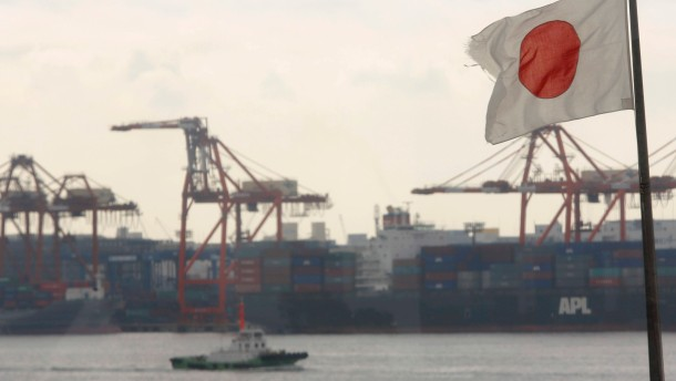 A Japanese flag flutters in front of a shipping container area, at a port in Tokyo