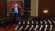 Die Abgeordneten sehen auf einer großen Video-Leinwand, wie Staatschef Xi Jinping den Volkskongress verfolgt.