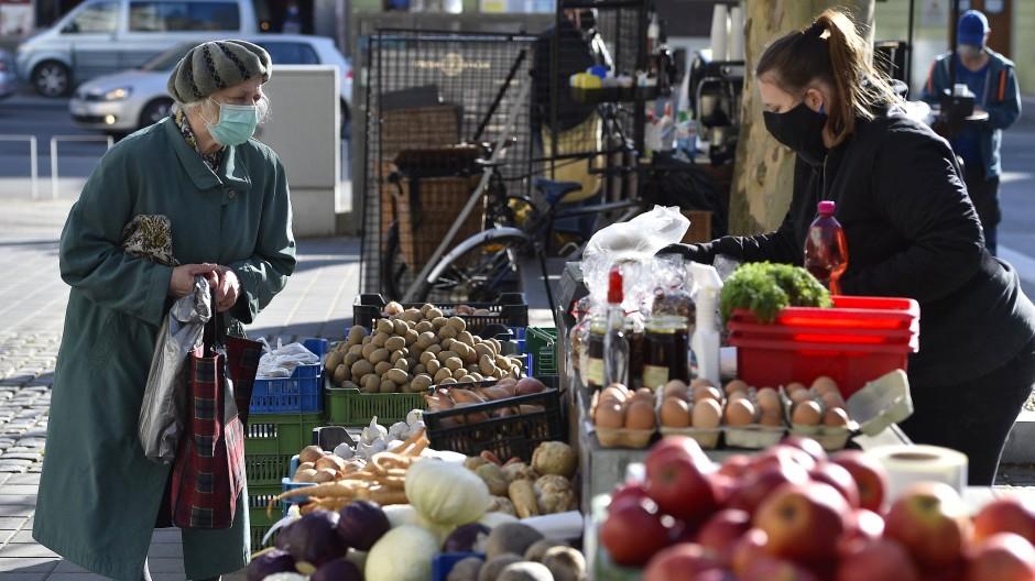 Eine Frau mit Mundschutz verkauft Lebensmittel auf dem Bauernmarkt im tschechischen Brno.