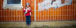 Ein kleines Mädchen spielt in einer Plattenbausiedlung allein mit seiner Puppe: Besonders in Berlin und Bremen leben viele Kinder in Abhängigkeit von Hartz IV.