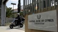 Ein Roller-Fahrer verlässt in Nikosia das Gelände der zyprischen Zentralbank.