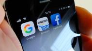 Logos für Apps der Internetkonzerne Google (von links), Amazon und Facebook sind auf dem Display eines iPhone zu sehen.