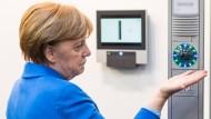 Die Kanzlerin testet bei ihrem Rundgang einen biometrischen Handvenenscanner. Erkennt das Gerät die richtige Handfläche, öffnet er zum Beispiel eine Tür. Bei der Kanzlerin hat es nicht funktioniert.