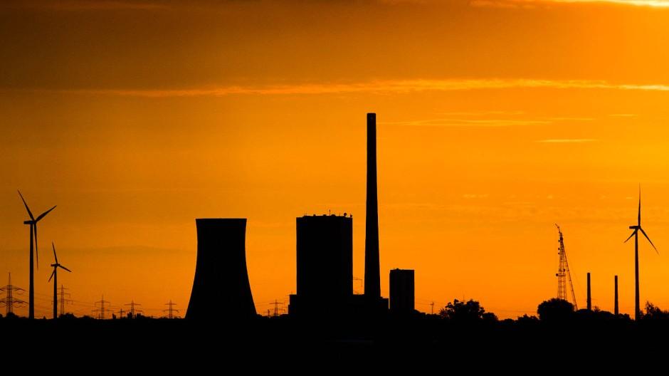 Die aufgehende Sonne taucht den Himmel über dem Steinkohlekraftwerk Mehrum bei Hohenhameln (Niedersachsen) in warmes Licht.