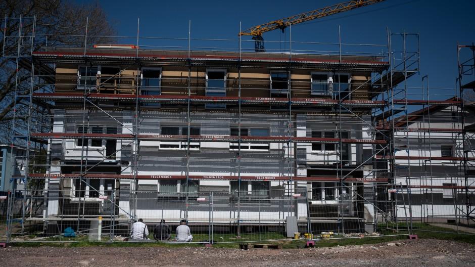 Arbeiter sitzen in der Mittagszeit vor einem Gebäude in Bochum im Innovationsquartier für Klimaschutz des Immobilienkonzerns Vonovia, das energetisch saniert wird.