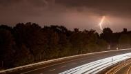 Wetterleuchten zuckt über eine Autobahn nahe Frankfurt.
