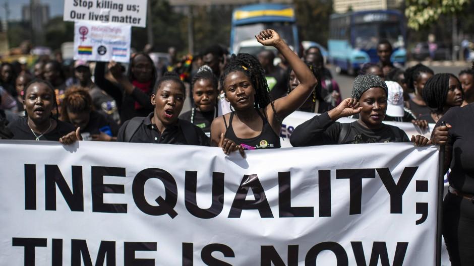"""Demonstrierende am 17. Januar in Nairobi: Mit einem Banner mit der Aufschrift """"End Inequality; Time is Now"""" gehen die Kenianer auf die Straße, um für gerechtere Lösungen in Wirtschafts- und Menschenfragen zu protestieren."""