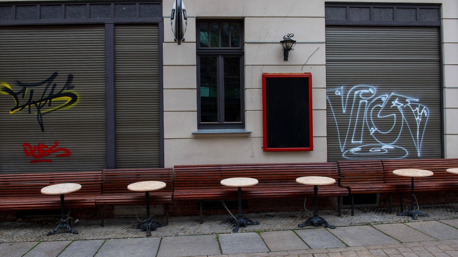 Leere Tische und Bänke stehen vor einer Kneipe in der Altstadt von Halle/Saale.