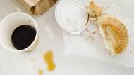 Ein Kaffee zum Mitnehmen und ein schnelles Brötchen - für viele Büroarbeiter ist das durchaus Alltag.