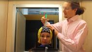 Hier trägt ein Forscher Kontaktgel auf die Elektroden einer EEG-Kappe auf, damit die Hirnsignale besser übertragen werden können.