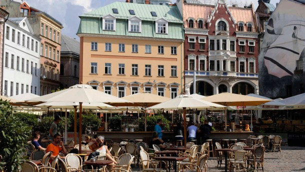 Tourists rest at the open-air cafe in downtown Riga