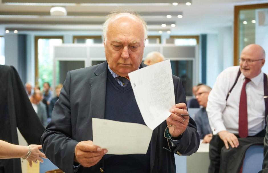 Der frühere Vorstand von Carlsberg Deutschland Wolfgang Burgard blättert im Gerichtsaal des Oberlandesgerichts Düsseldorf in seinen Unterlagen.