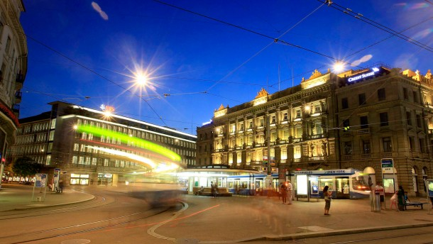 Trams drive past offices of Swiss banks UBS and Credit Suisse at Paradeplatz square in Zurich