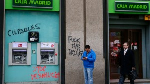 People stand in front of a Bankia bank branch covered with graffiti in downtown Madrid