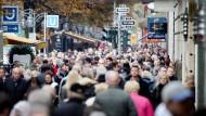 Menschen drängen sich am an einem verkaufsoffenen Sonntag über die Einkaufsstrasse Königsallee in Düsseldorf.