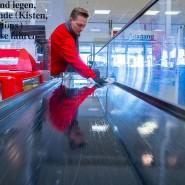 Wichtiges Glied in der Versorgungskette: Ein Kassierer im Supermarkt reinigt das Warenband mit Desinfektionsmittel.