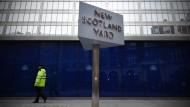 """Vor dem Bürohaus wacht das berühmte, sich drehende dreieckige Schild mit der Aufschrift """"New Scotland Yard""""."""