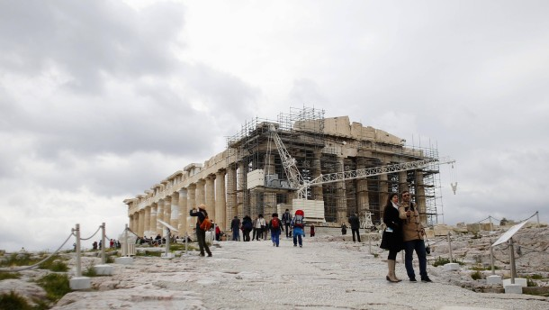 Tourists take a selfie in front of the temple of Parthenon atop Acropolis hill in Athens