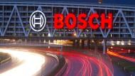 Autos fahren am Stuttgarter Flughafen auf der Autobahn A8 unter einer Brücke mit dem Bosch-Logo entlang.