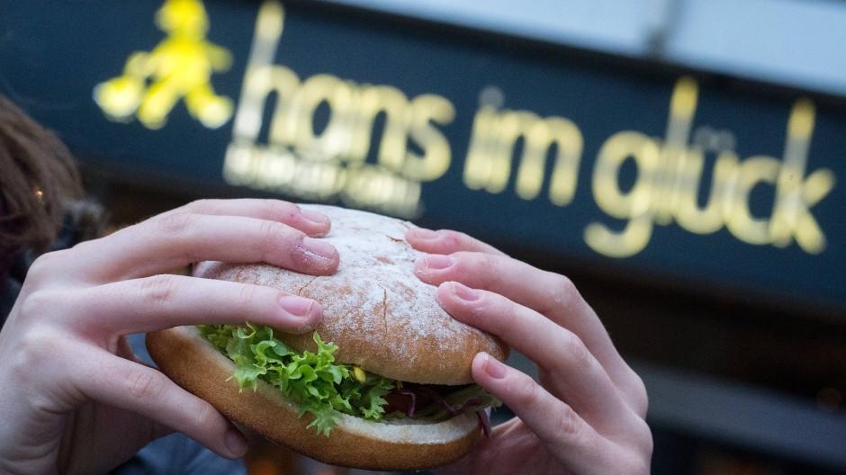 Eine junge Frau hält einen vegetarischen Burger der Burger-Kette Hans im Glück in der Hand. Die Kette bekommt einen neuen Eigentümer.