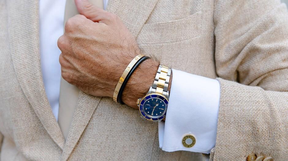 Sichtbarer Wohlstand: Ein Mann trägt eine teure Armbanduhr und Goldschmuck.