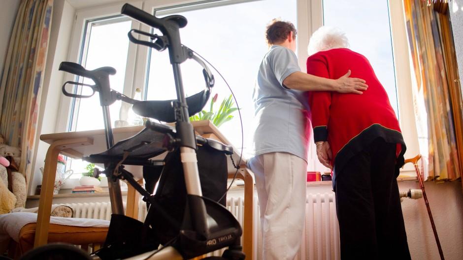 Eine Pflegerin und eine Bewohnerin des Pflegeheims schauen zusammen aus einem Fenster.