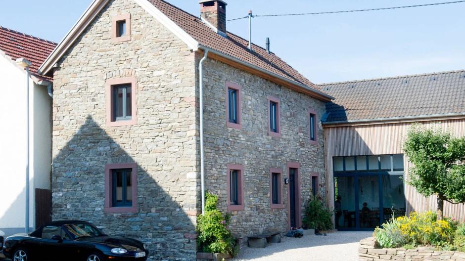 Freigelegt und erweitert: Das alte Steinhaus ist heute wieder als solches zu erkennen, die einstige Scheune trägt eine Holzverschalung.