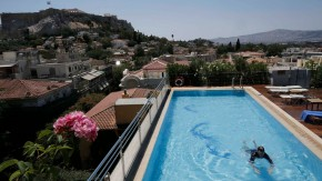 A tourist swims in the pool of a luxury hotel in Athens