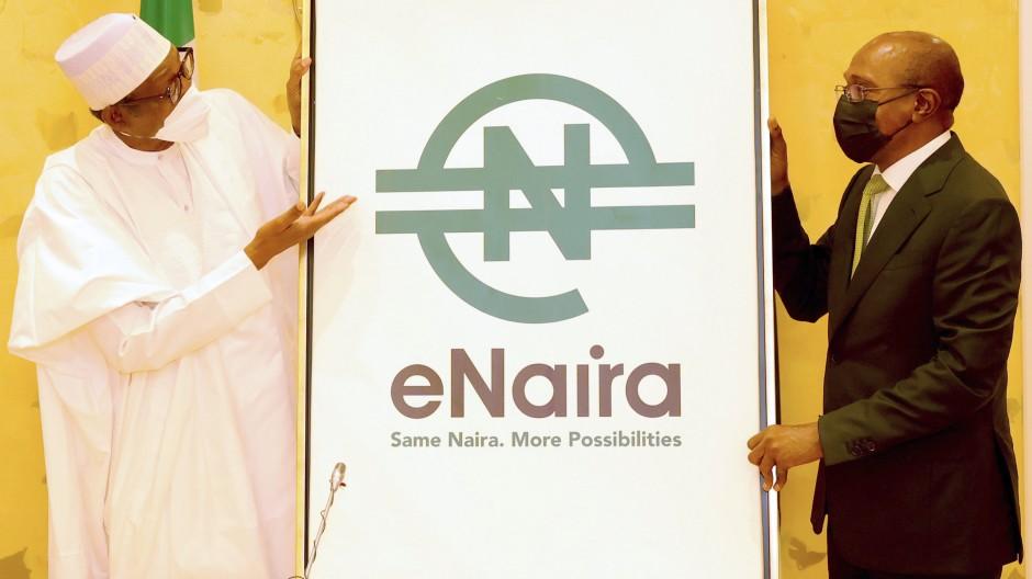 Muhammadu Buhari (l), Präsident von Nigeria, und Godwin Emefiele, Gouverneur der Zentralbank,präsentieren ein Plakat zur Einführung des eNaira.