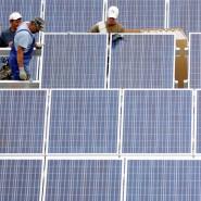 Lohnende Investition: Arbeiter montieren Module auf einem Solarfeld