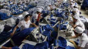 Employees work at a production line of a garment factory in Huaibei