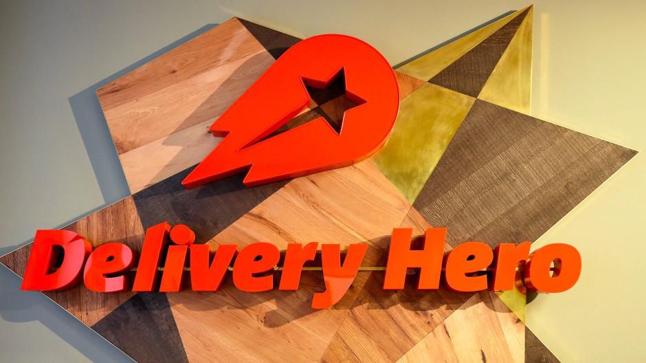 Das Logo von Delivery Hero hängt in der Zentrale der Bestell-Plattformen für Essen: Das Unternehmen könnte bald in den Dax aufsteigen.