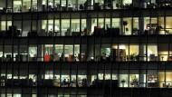 In vielen Fenstern brennt noch Licht: In so manchem Job gelten unbezahlte Überstunden als eine Selbstverständlichkeit.