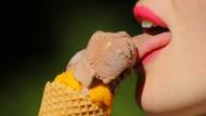 Eine Frau genießt in Berlin eine Waffel mit Schokoladen- und Mangoeis.