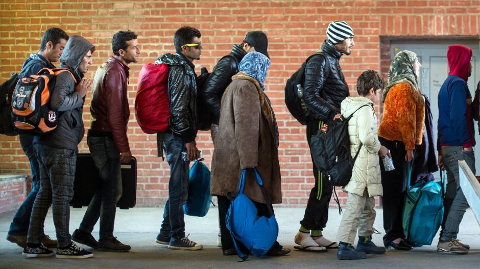 Flüchtlinge warten auf ihre Weiterfahrt zur Unterkunft. (Symbolbild)