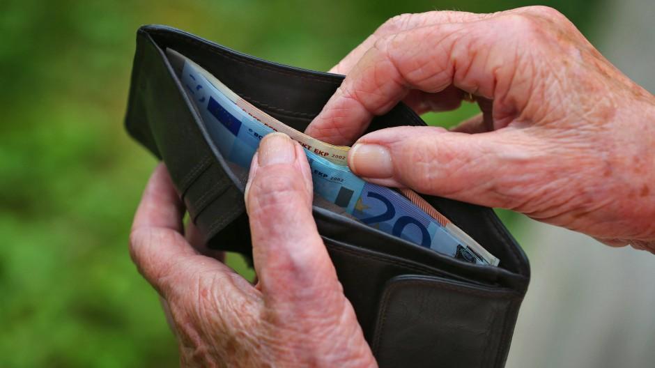 Eine Rentnerin hält einen Geldbeutel mit verschiedenen Euroscheinen. Frauen erhalten im Schnitt weniger Rente als Männer.