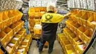 Eine Mitarbeiterin der Deutschen Post sortiert Großbriefe im Briefzentrum.