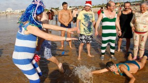Participants joke before taking their first bath in the sea to celebrate the arrival of the New Year at Carcavelos beach