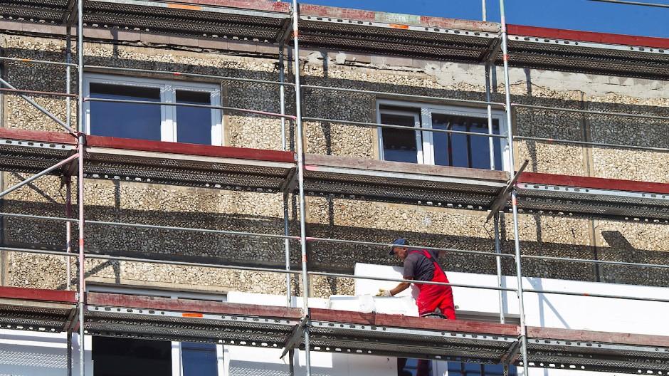 Die Fassade eines Wohnhauses wird gedämmt.