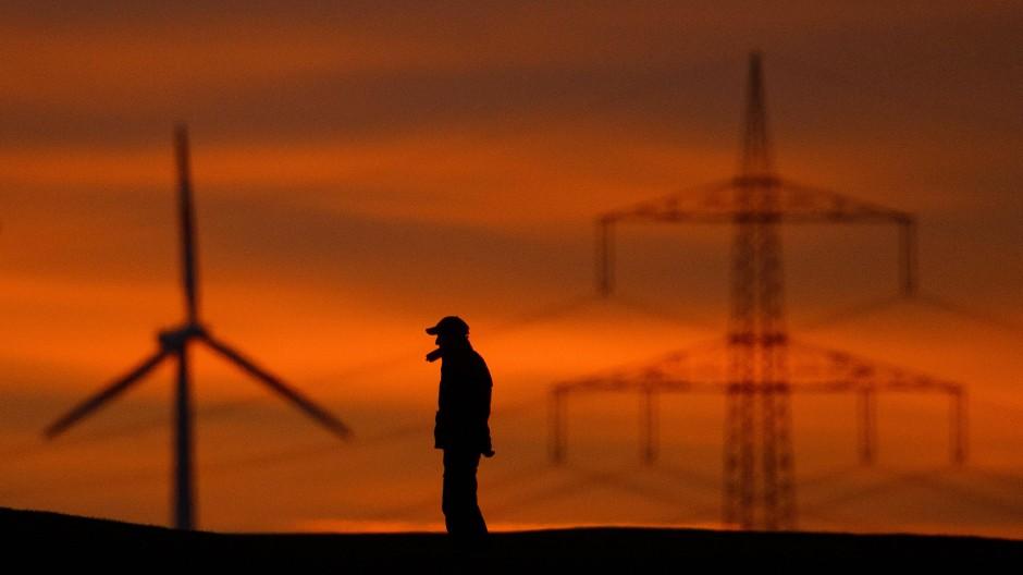 Silhouetten von Windrädern und einer Hochspannungsleitung in Sehnde-Rethmar in der Region Hannover