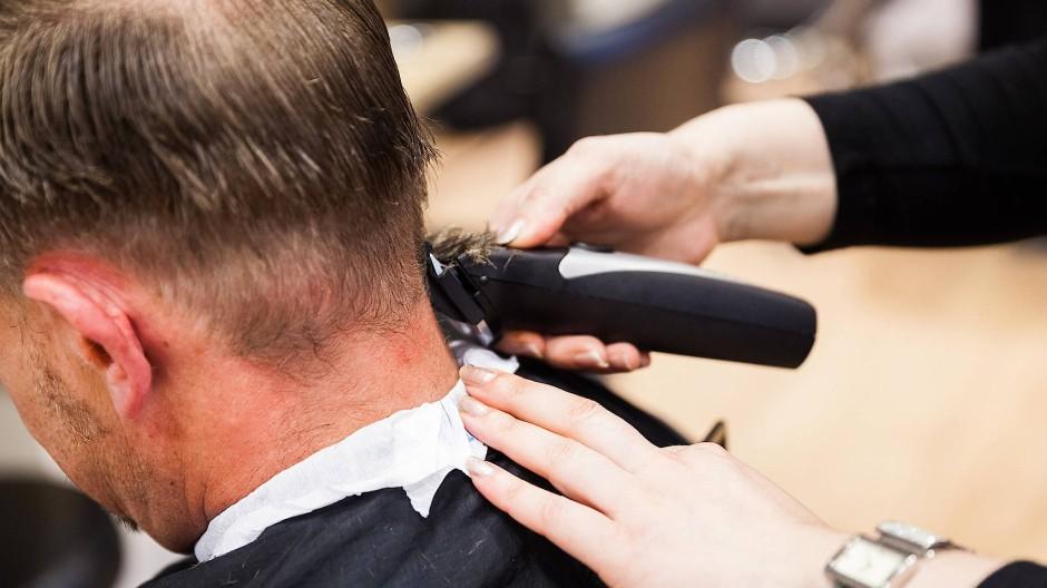 Eine Friseurin rasiert einem Kunden die Haare.