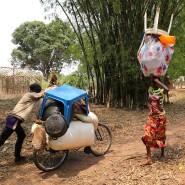 Kongolesische Einwanderer in Angola transportieren ihre Habseligkeiten mit einem geliehenen Fahrrad.