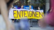 Demonstrantinnen stehen am Morgen vor dem Eingang zur Hauptversammlung des Immobilienkonzerns Deutsche Wohnen