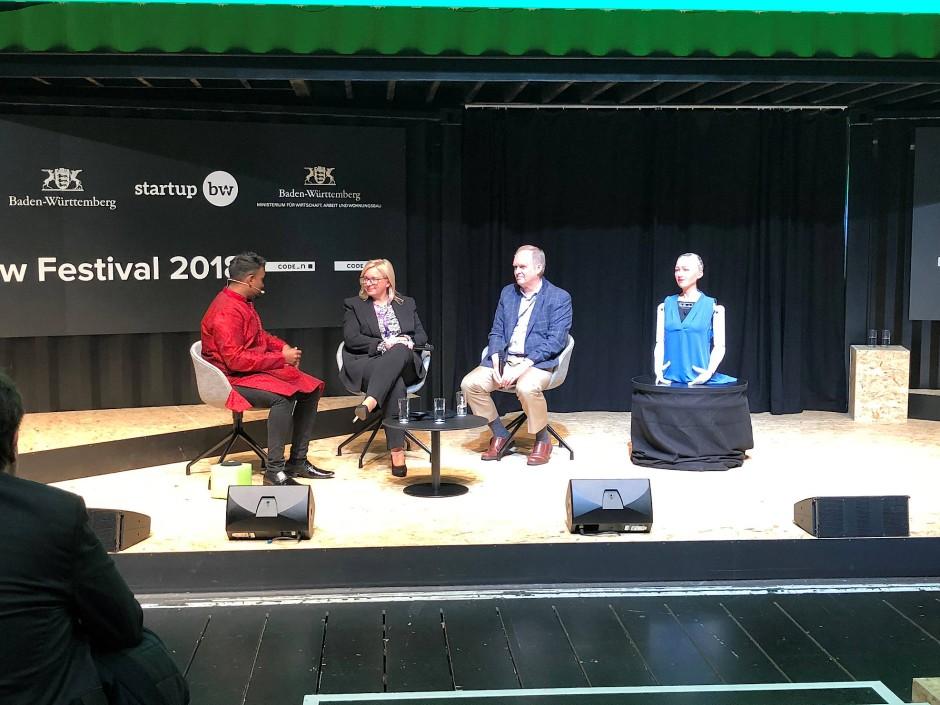 Auf der Bühne: Sophia, der humanoide Roboter, Professor Robin Hanson und Marika Lulay, CEO von GFT (von rechts).