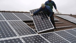 Workers install solar panels on the roof of a kindergarten in the town of Falkensee near Berlin