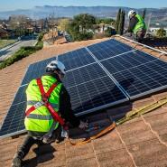 Arbeiter installieren eine Solaranlage auf einem Dach in Spanien.