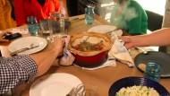Der Hühnereintopf kommt dampfend auf den Tisch.